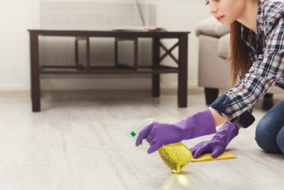 Concentrated woman polishing wooden floor