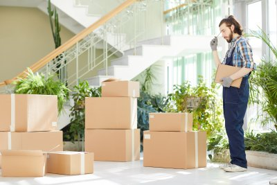 Pensive moving specialist counting delivered boxes