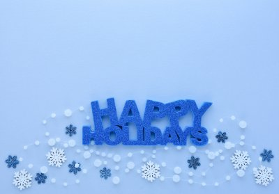 """Christmas or New Year greeting card. Greeting """"Happy Holidays"""" and snowflakes on pastel blue background. Flat lay, top view, copy space"""