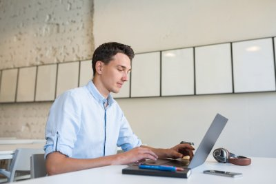 young handsome smiling man sitting in open space office working on laptop